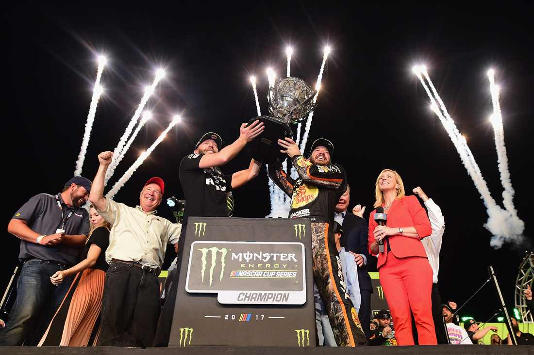 Martin Truex Jr and his crew chief Cole Pearn lifting the Monster Energy NASCAR Championship Trophy